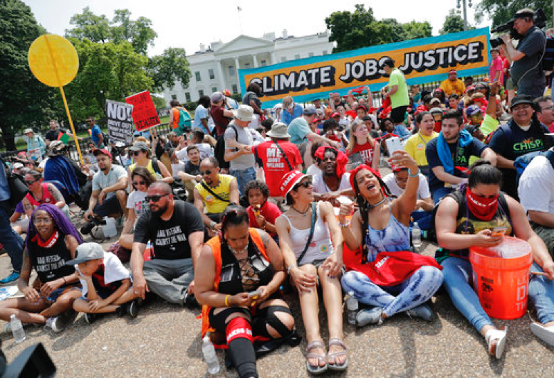 Demonstrators+sit+on+the+ground+along+Pennsylvania+Ave.+in+front+of+the+White+House+in+Washington%2C+Saturday%2C+April+29%2C+2017%2C+during+a+demonstration+and+march.+Thousands+of+people+gathered+across+the+country+to+march+in+protest+of+President+Donald+Trump%27s+environmental+policies%2C+which+have+included+rolling+back+restrictions+on+mining%2C+oil+drilling+and+greenhouse+gas+emissions+at+coal-fired+power+plants.+The+demonstrators+sat+down+for+100+seconds+to+mark+President+Trump%27s+first+100+days+in+office.+%28AP+Photo%2FPablo+Martinez+Monsivais%29