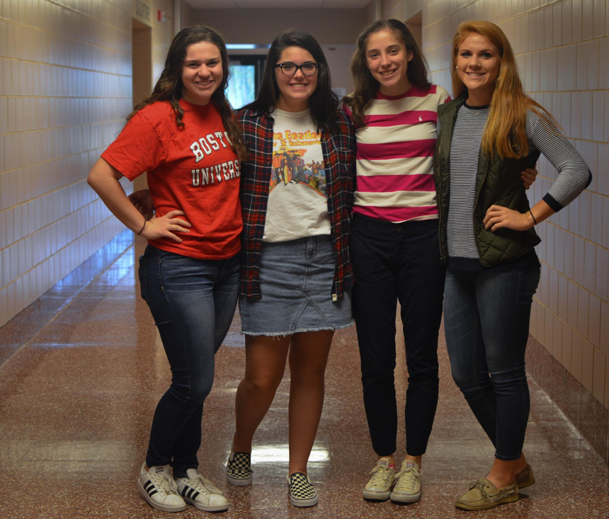 Left to right, Maria Goldman, Kaitlin Christ, Evie Gentile, Grace Murray, seniors, pose for a quick photo to show off their fall outfits. Goldman rocks a Boston University shirt with casual jeans. Christ wears a jean skirt with a t-shirt and a flannel to add some pizazz to her look. Gentile styles a simple pink and white striped shirt with jeans for the school day, while Murray put on jeans with a striped shirt and a vest. All four wear various types of casual shoes to match their outfits. (Broadcaster/Elaina Joyner)