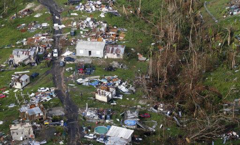 In this aerial photo damaged and destroyed homes are seen in the aftermath of Hurricane Maria in Toa Alta, Puerto Rico on Sept. 28, 2017. 46 percent of the 3.4 million residents remain without power 70 days after Hurricane Maria. (AP Photo/Gerald Herbert)