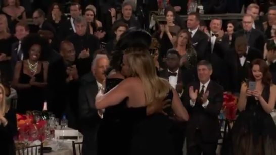 Oprah Winfrey and Reese Witherspoon embrace after Witherspoon presents the Cecil B. DeMille award to Winfrey for outstanding contributions to the world of entertainment. Winfrey was the first black woman to receive this award. (Golden Globe Awards Twitter)