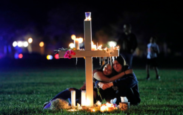 Two people comfort each other as they sit and mourn at one of seventeen crosses, after a candlelight vigil for the victims of the Wednesday shooting at Marjory Stoneman Douglas High School, in Parkland, Fla., Thursday, Feb. 15, 2018. Nikolas Cruz, a former student, was charged with 17 counts of premeditated murder on Thursday. (AP Photo/Gerald Herbert)