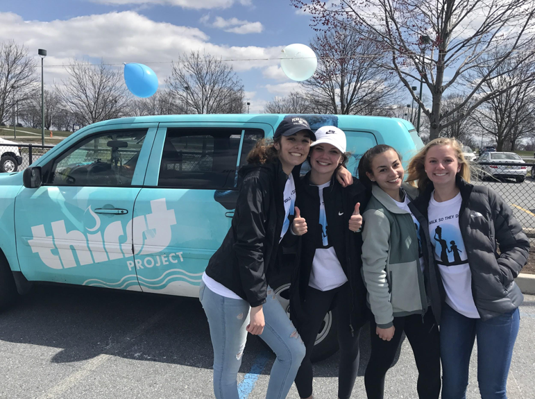 From left to right, sophomores, Leah Koppenhaver, Katherine Clark, Claire Sheppard, and Olivia Bratton, stand in front of the Thirst Project car. The Thirst Project has raised money to build 1,754 wells in 13 countries to save a total of 285,599 lives. (Broadcaster/Clare Canavan)