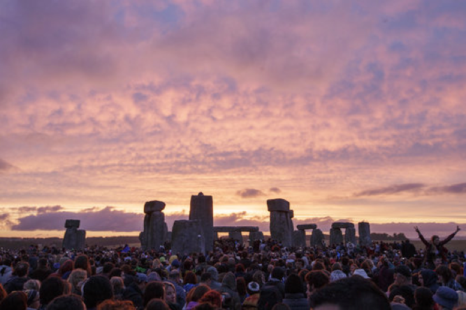 In this Sunday, June 21, 2015 file photo, the sun rises as thousands of revellers gather at the ancient stone circle Stonehenge to celebrate the Summer Solstice, the longest day of the year, near Salisbury, England. British authorities have approved a contentious road tunnel under Stonehenge but have altered its route so it doesn't impede views of the sun during the winter solstice, it was reported on Tuesday, Sept. 12, 2017. (AP Photo/Tim Ireland)