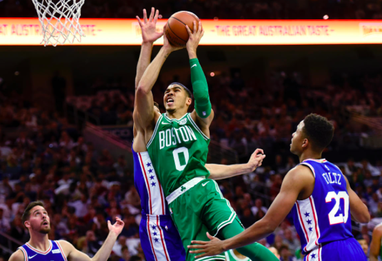 Jayson Tatum, small forward for the Celtics, drives through the the 76ers to score. Tatum scored 25 points to send Boston to the win. (AP Photo/Michael Perez)
