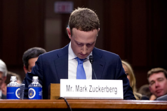Facebook CEO Mark Zuckerberg looks down as a break is called during his testimony before a joint hearing of the Commerce and Judiciary Committees on Capitol Hill in Washington, Tuesday, April 10, 2018, about the use of Facebook data to target American voters in the 2016 election. (AP Photo/Andrew Harnik)