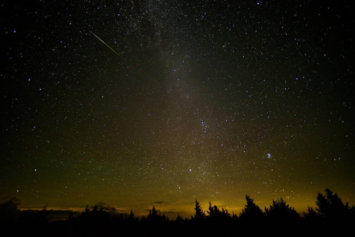 A meteor streaks across the sky during the annual Perseid meteor shower Friday, Aug. 12, 2016 in Spruce Knob, West Virginia. The Perseids, a meteor shower that occurs in mid July to mid August, is one of two meteor showers created by Halley's comet. (NASA)
