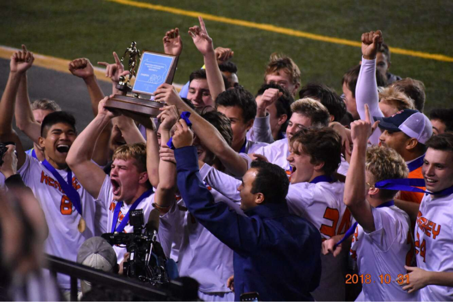 Hershey Boys Soccer celebrating with coach Andrew Maya after receiving the district championship trophy. The boys will take the field again first round of states Thursday, November 6. (Submitted by Brendan Kerr)