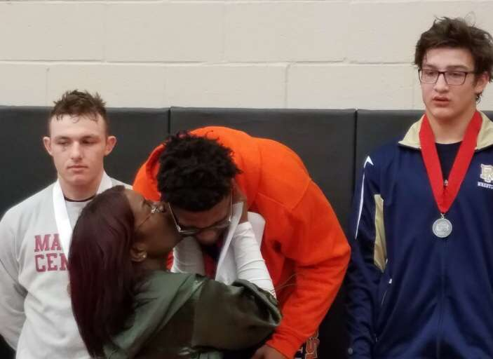 Nyiem Flucas's mother, Danielle Phillips, congratulates him following his match in sectional finals. Flucas won first place. (Submitted by Nyiem Flucas)