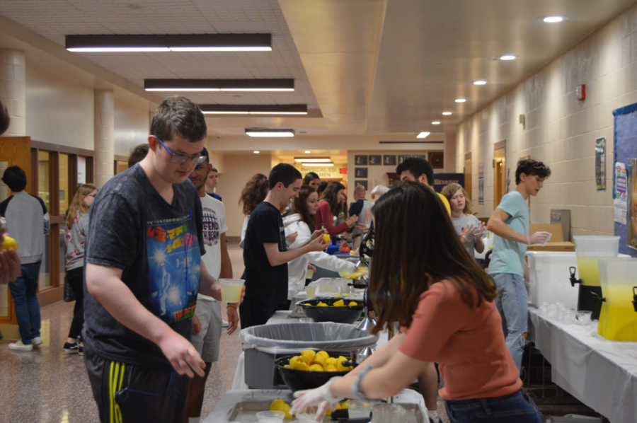 """Random Acts of Kindness Club members and volunteers pass out free drinks on April 17th, 2019. The students were asked to imagine the lemons as their problems or write them on the lemon before squeezing it into their cups and throwing their """"problems"""" away. (Broadcaster/Alina Zang)"""