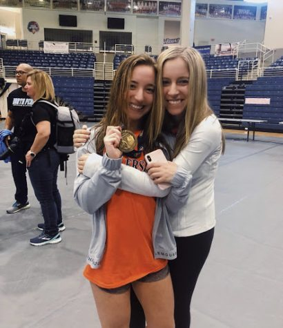 Gould is celebrating her sixth place finish with her sister. This was Gould's final match as a Trojan. (Submitted by Meredith Gould)