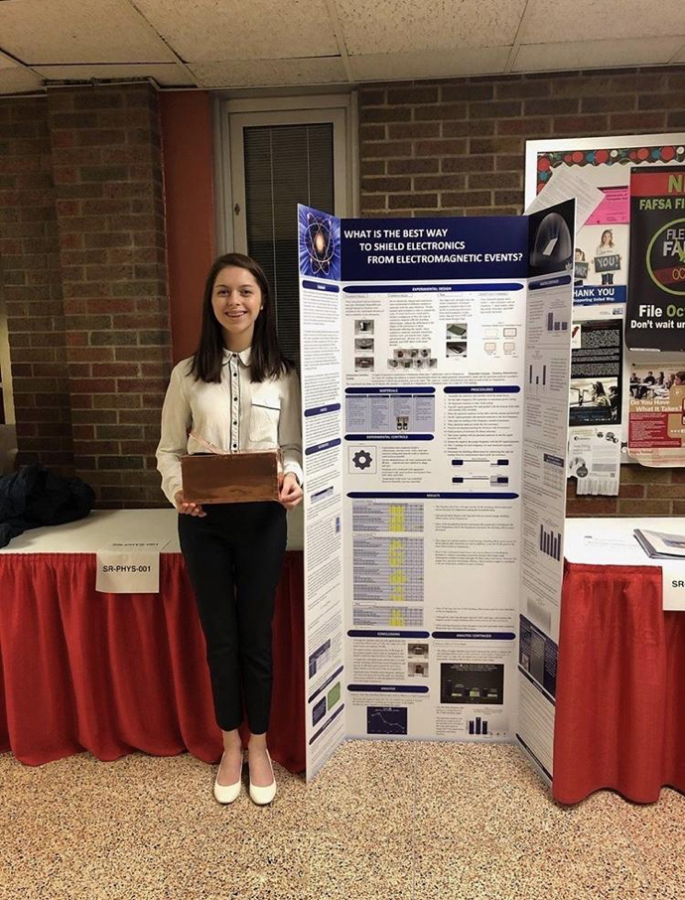 Taylor Koda stands next to her science fair project at the awards ceremony on March 4, 2019. Koda won several awards at the science fair, including the award for Most Outstanding Exhibit in Material Sciences. (Taylor Koda)
