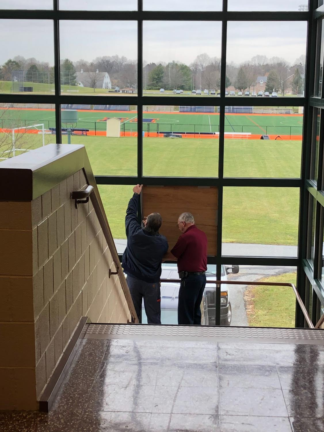 Custodians tape wood to secure the broken window on Monday, January 13, 2019. The stairway in the F wing was closed off to keep students safe. (Broadcaster/Eva Baker)