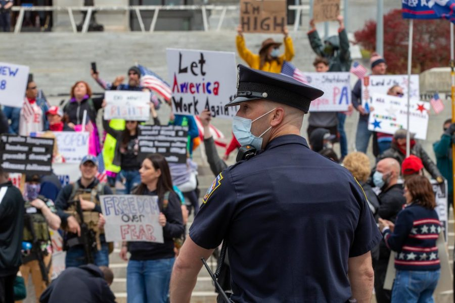 A Harrisburg city police officer watches the ReOpen PA Protest on Monday, April 20, 2020.  Police estimated the number of protesters to under 1,000, or 0.00078 percent of the Pennsylvania population.  (Paul Weaver/ CC BY-NC-SA 2.0)