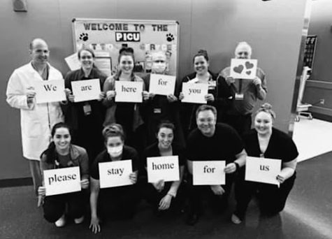 Dr. Brian Clark (top left) holds up a sign with other medical workers at the Penn State Health Medical Center. Dr. Clark is a Pediatric Cardiac Surgeon. (Submitted by Kate Clark)