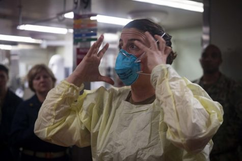 Lt. Cmdr. Nevin Yazici demonstrates how to properly fit an N95 respiratory protective device aboard the hospital ship USNS Comfort in New York harbor on March 31, 2020.  The N95 mask or any mask must fit tightly against the face to offer protection.  (U.S. Navy/Mass Communication Specialist 2nd Class Sara Eshleman/CC BY 2.0)