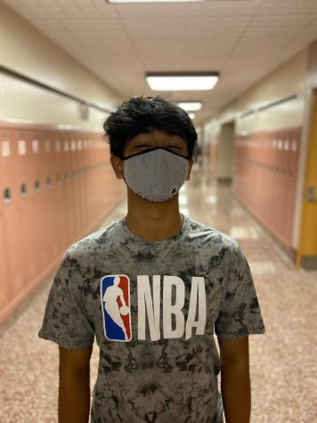 Sophomore Dinesh Tamang wears a grey Champion mask to school. Students who do not comply with mask requirements are required to participate in virtual learning. (Broadcaster/Molly Ziesenheim)