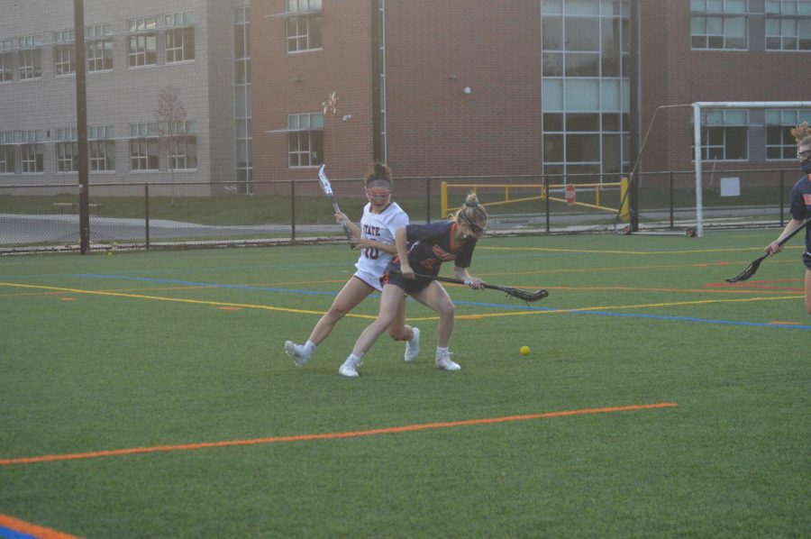 Caroline Glus, Junior #3,  encounters a ground ball her way. An opposing player waits right behind her. ( Broadcaster/Allyson Lin)