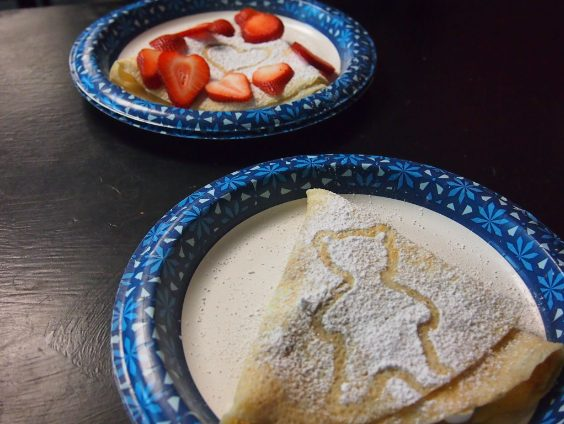 A pair of sweet dessert crepes decorated with powdered sugar. The powdered sugar designs help differentiate which crepe is which. (Broadcaster/Anna Callahan)