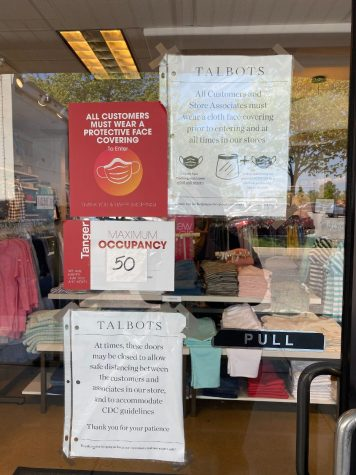 Stores notify shoppers that mask and occupancy guidelines are being followed. Occupancy and mask protocol had been frequently posted on the signs of storefronts at the outlets. (Broadcaster/Keela Delves)